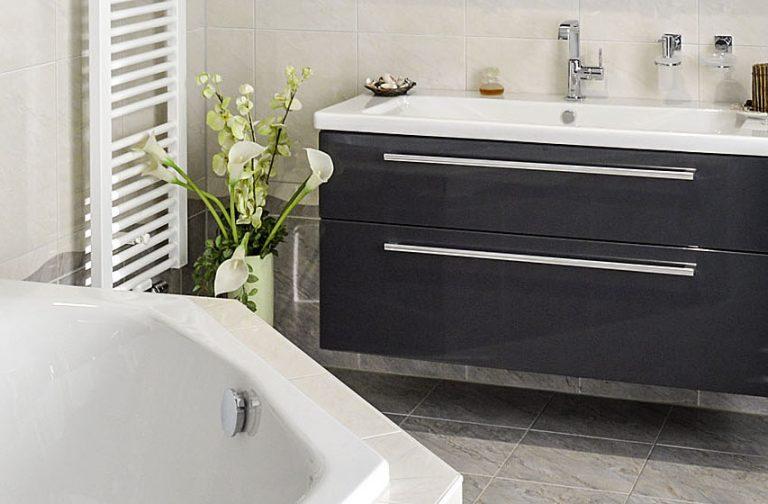 Abbildung Badewanne und Waschtisch mit schwarzem Unterschrank