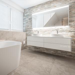 Badezimmer mit Fliesen in Natursteinoptik und elegantem Waschtisch